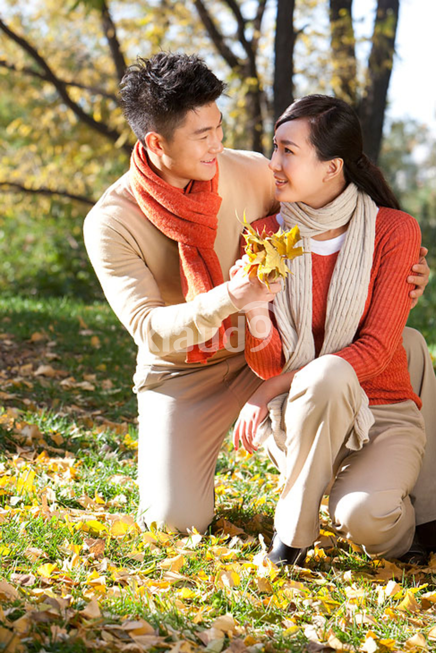 Young Chinese couple with a collection of leaves in autumn