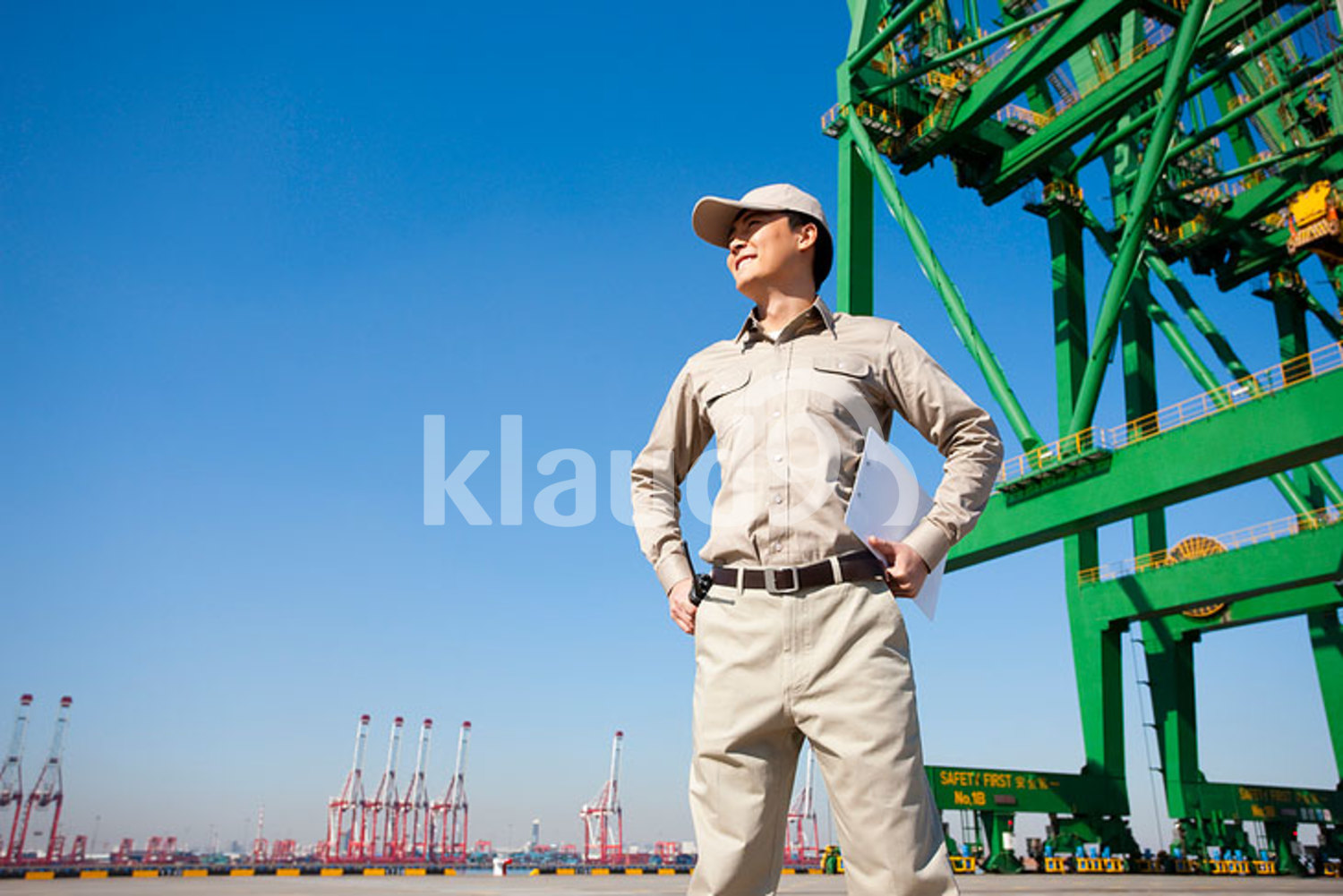 Male Chinese shipping industry worker with hands on hips with shipping dock background