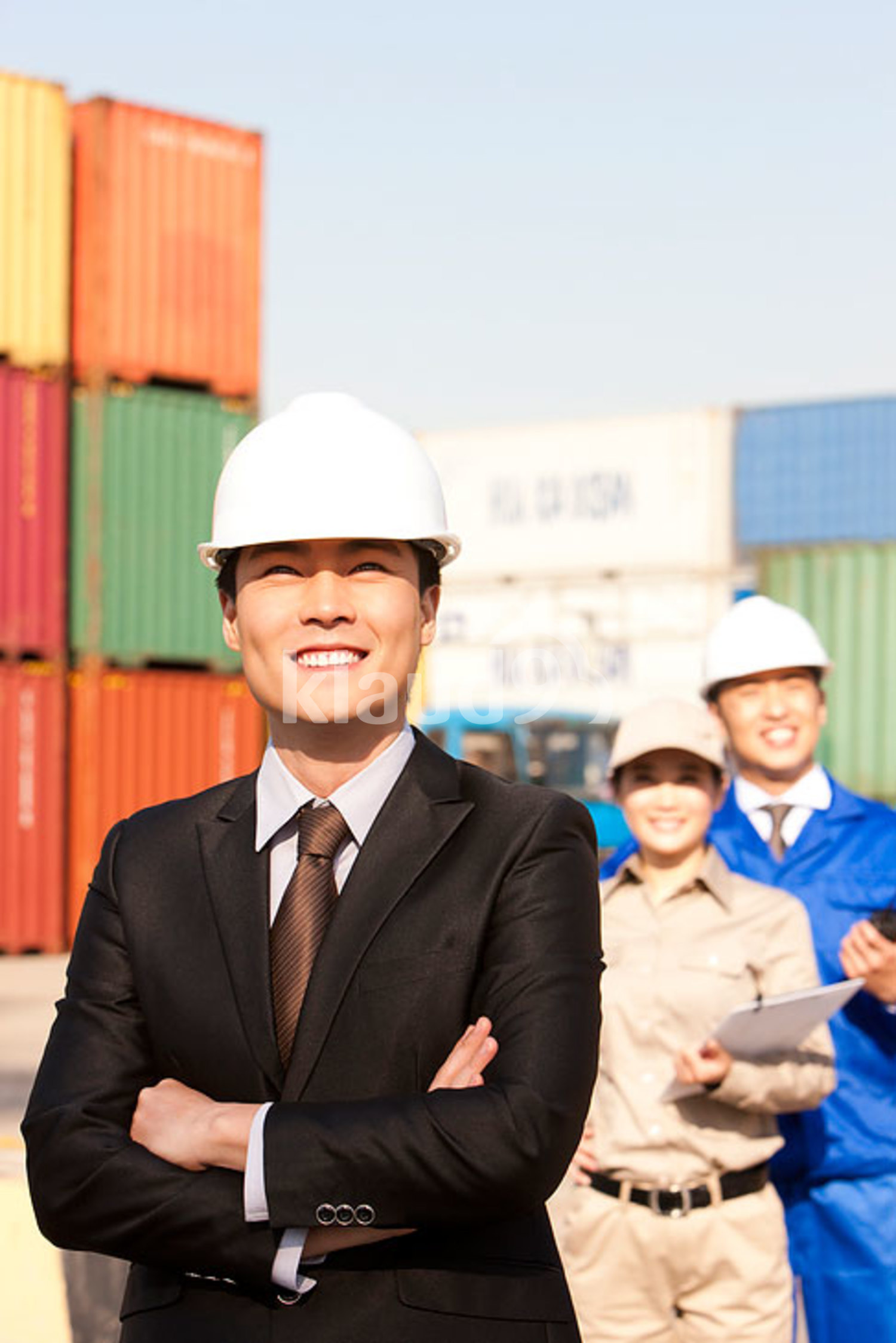 Chinese businessman with shipping industry workers in the background