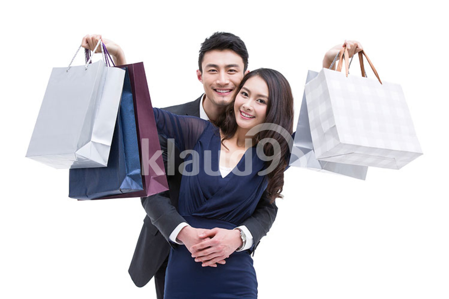 Happy young Chinese couple with shopping bags
