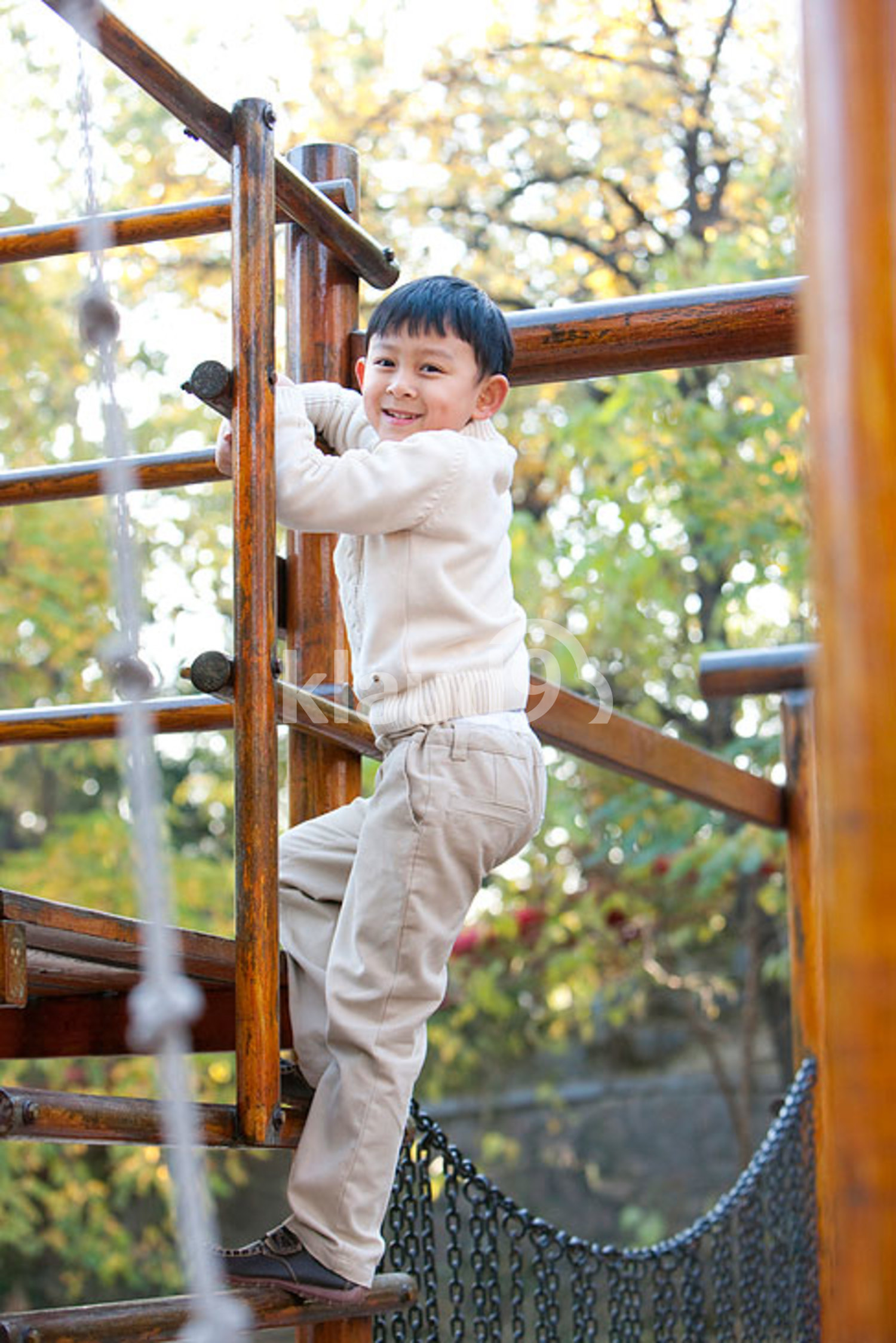Chinese boy climbing a ladder in a playground