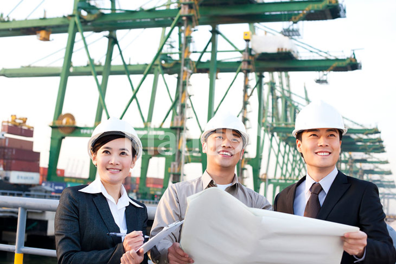 Chinese shipping industry professionals looking over blueprints in a row