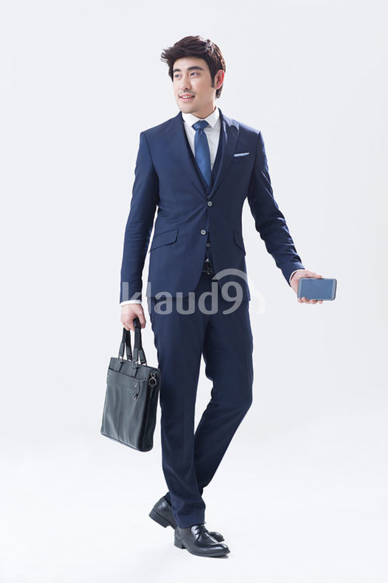 Young Chinese businessman holding a smart phone