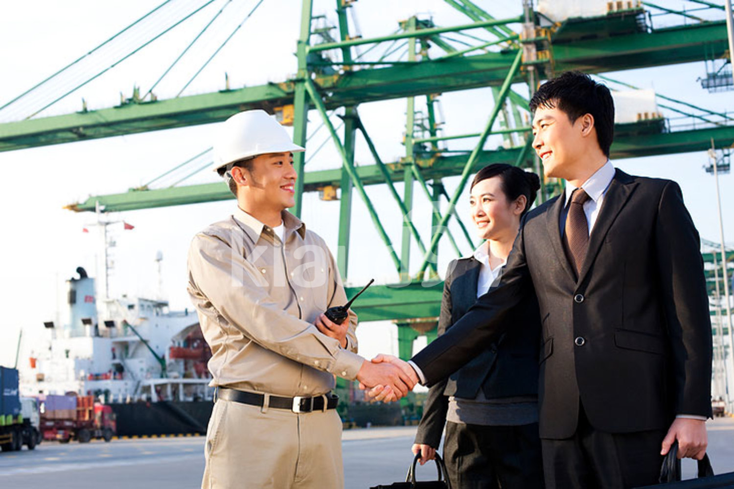 Chinese businesspeople and a shipping industry worker shaking hands at a shipping port