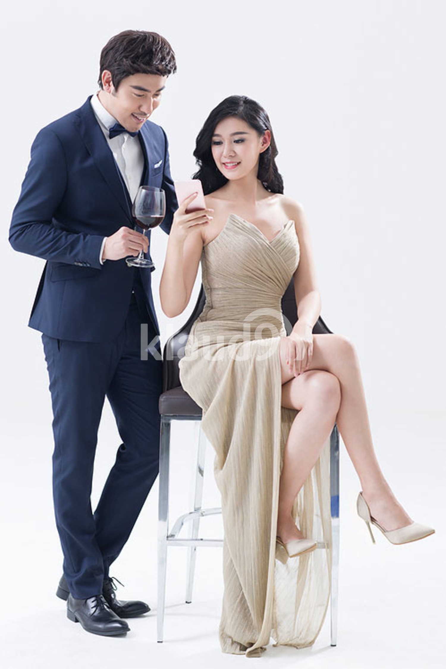 Elegant young Chinese couple using smart phone