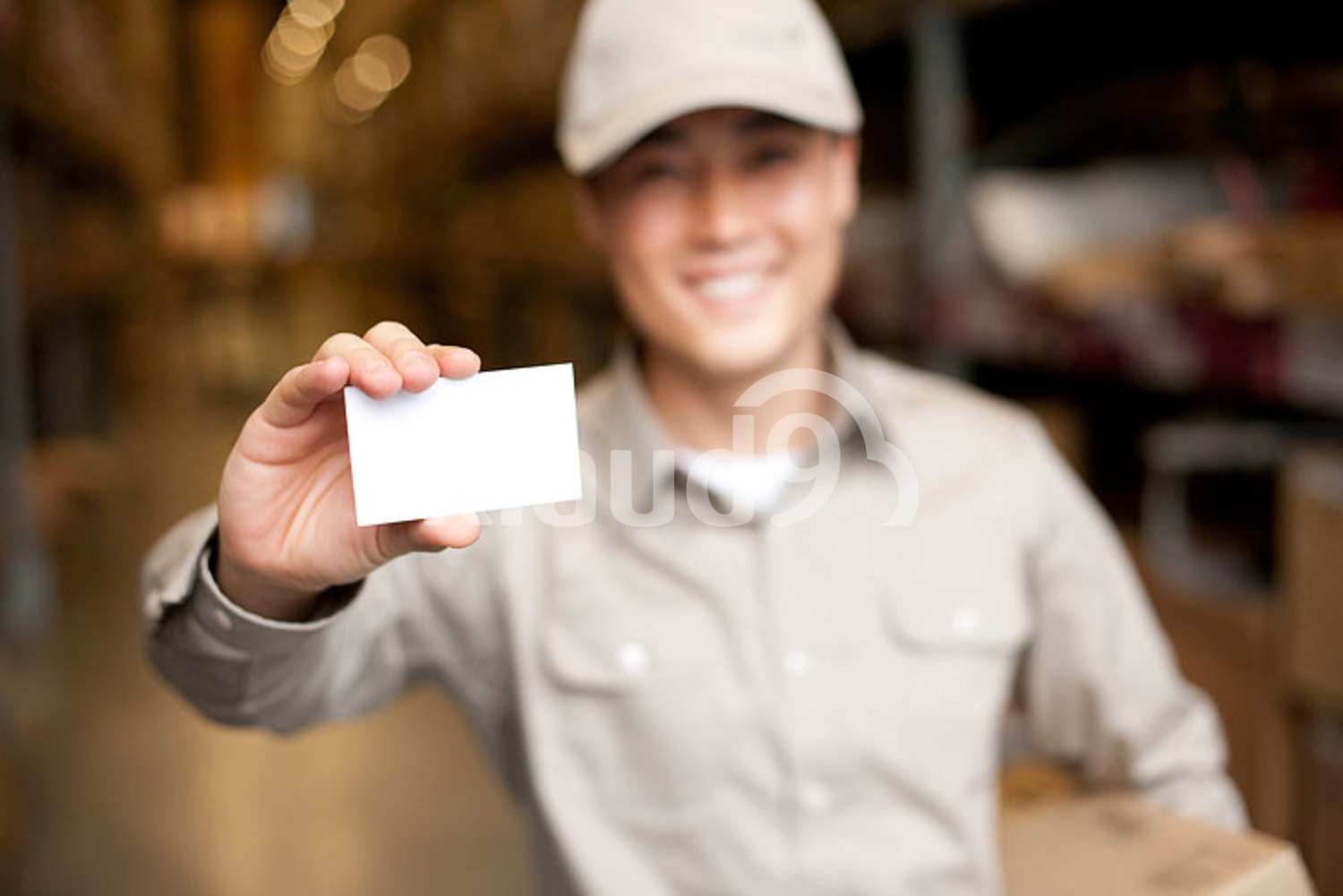 Male Chinese warehouse worker holding up a blank business card