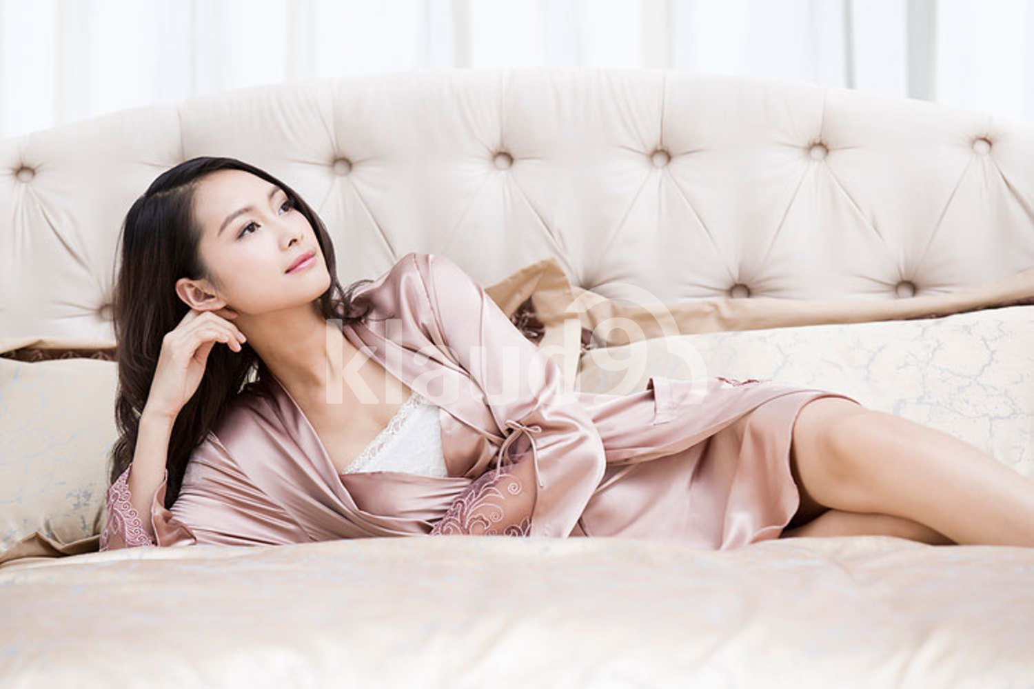 Elegant young Chinese woman lying in bed