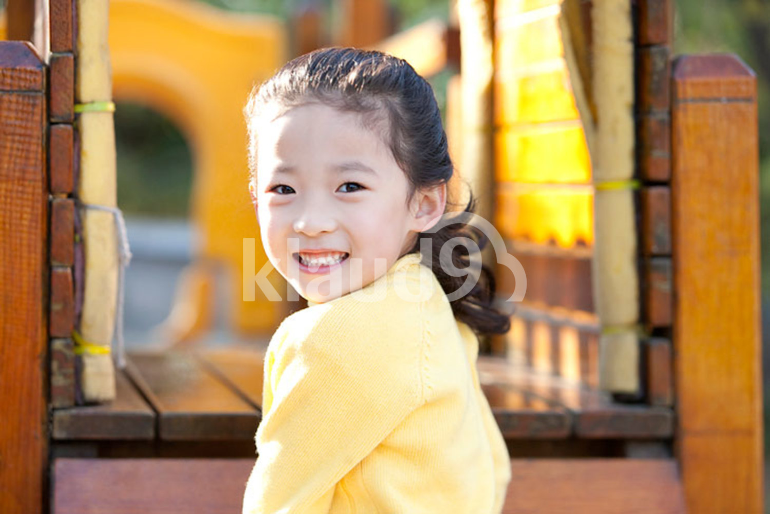Chinese girl playing on playground toys