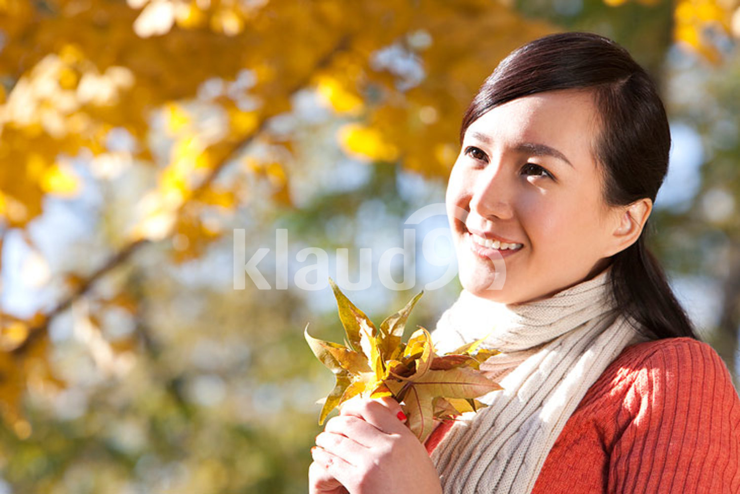 Young Chinese woman with a collection of leaves in autumn