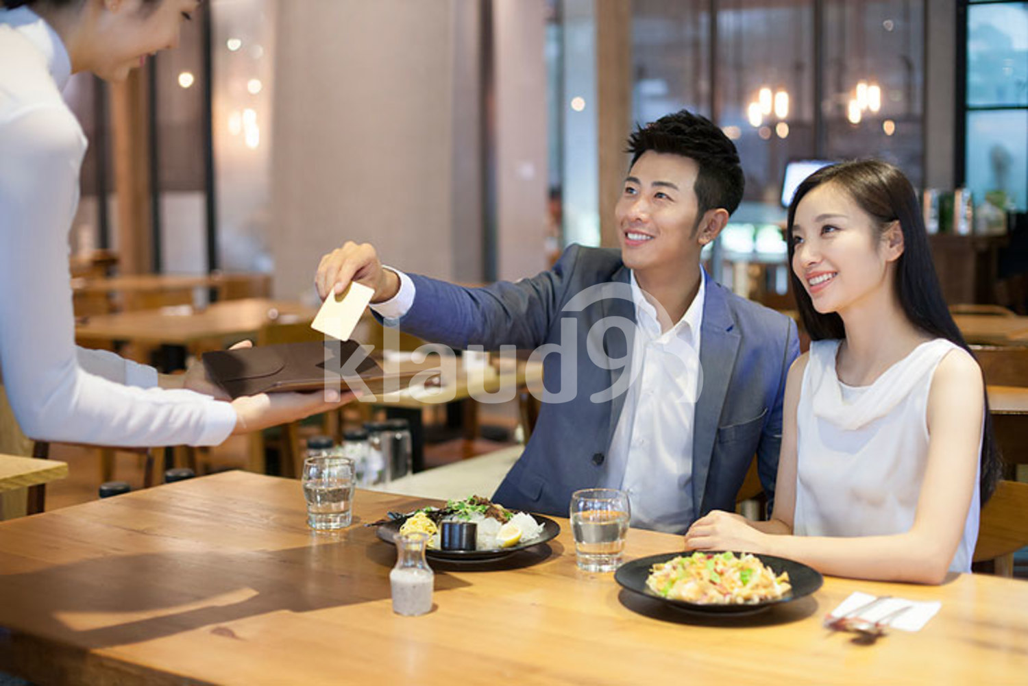Young Chinese man paying bill by credit card in restaurant