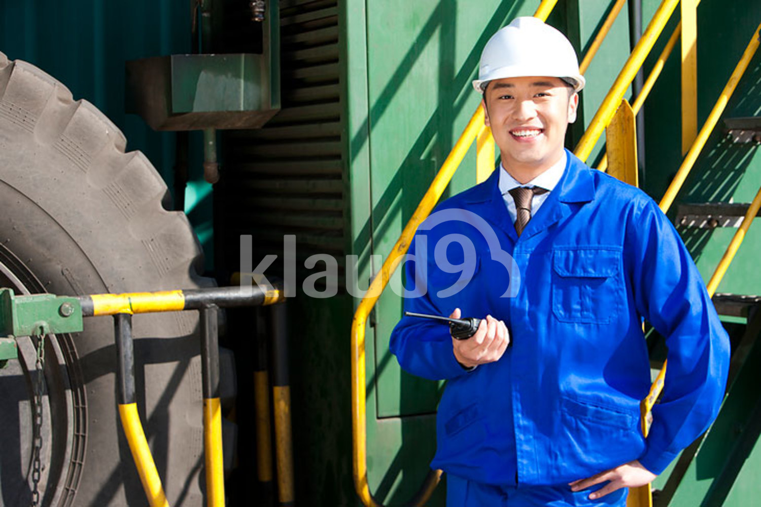 Chinese shipping industry manager with a walkie-talkie in front of a machine