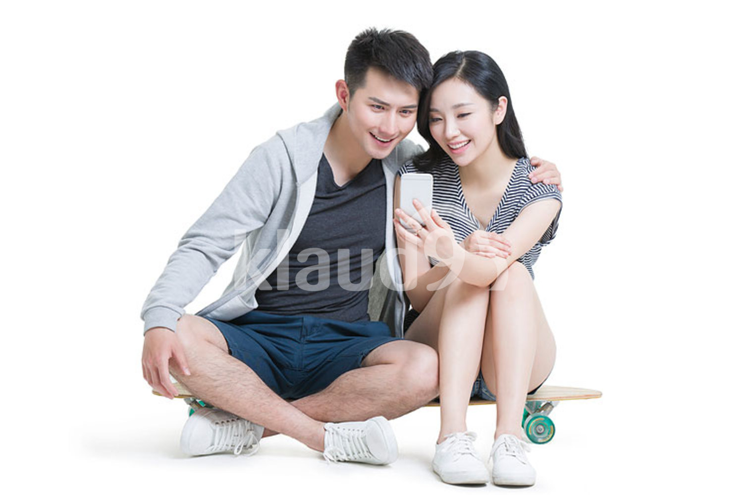 Happy young Chinese couple using smart phone