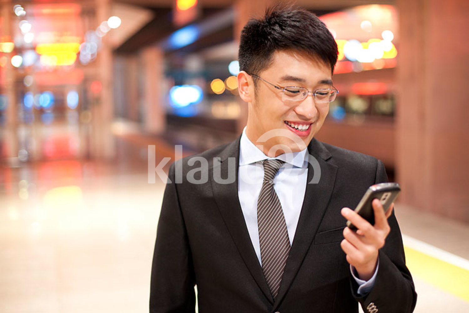 Young Chinese businessman using his mobile phone at the train station