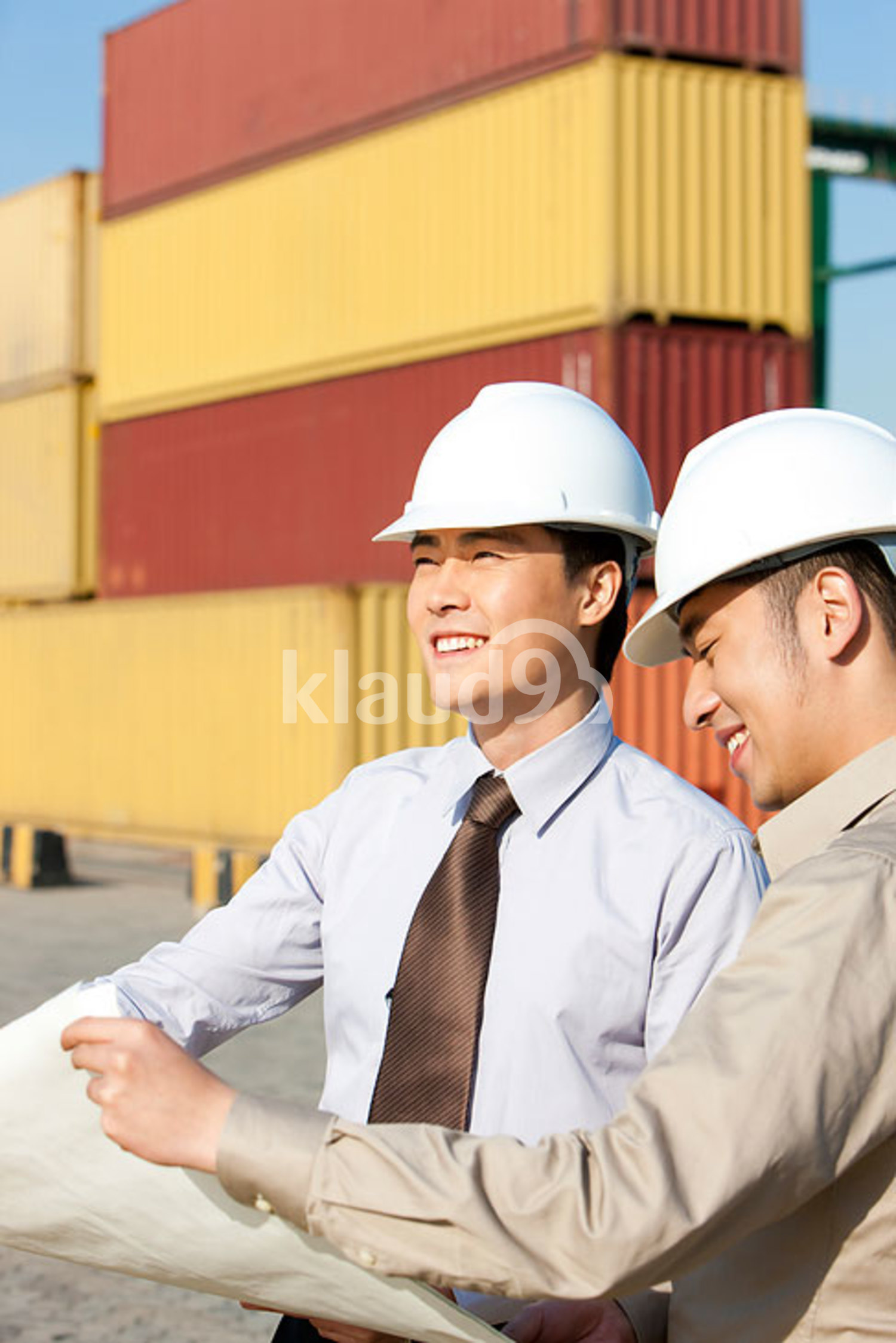 Chinese businessman with shipping industry worker looking over blueprints