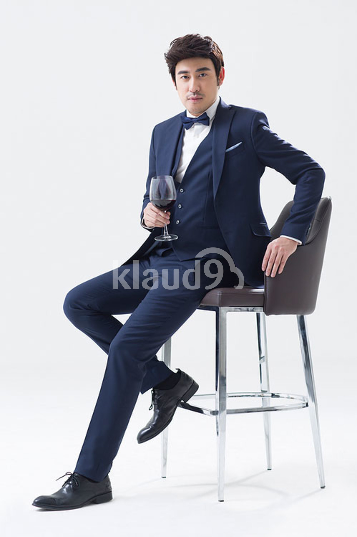 Elegant young Chinese man enjoying red wine