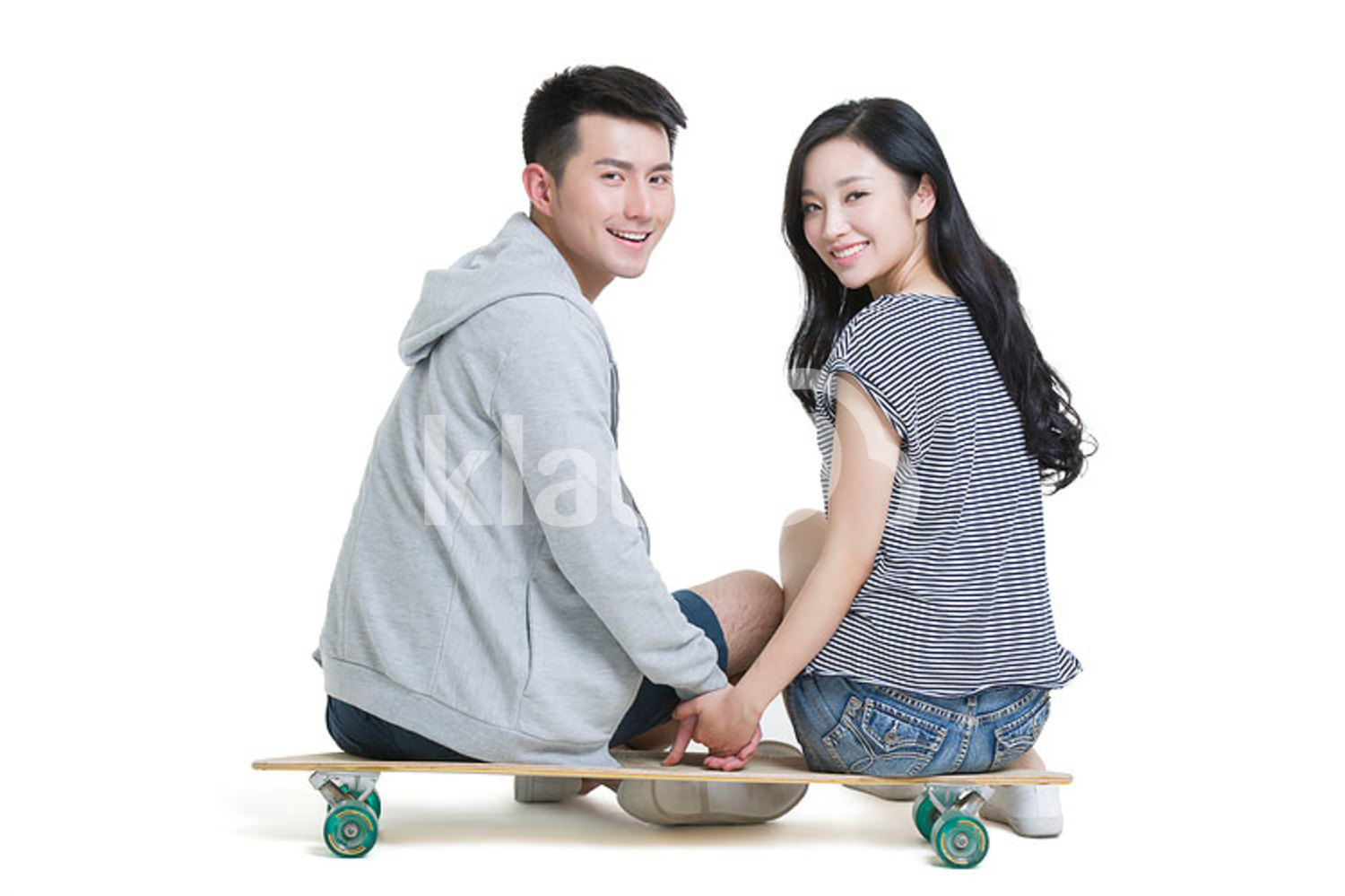 Happy young Chinese couple sitting on a skateboard