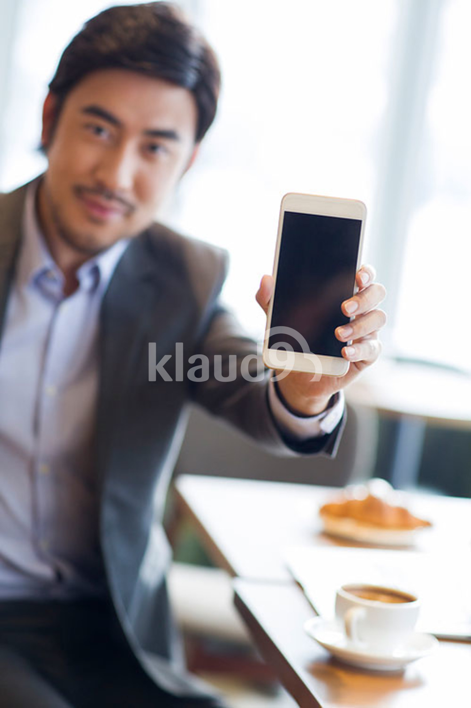 Chinese businessman showing smart phone in café