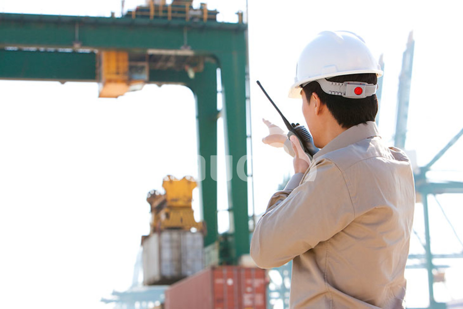 Chinese shipping industry worker directing cranes with his walkie-talkie