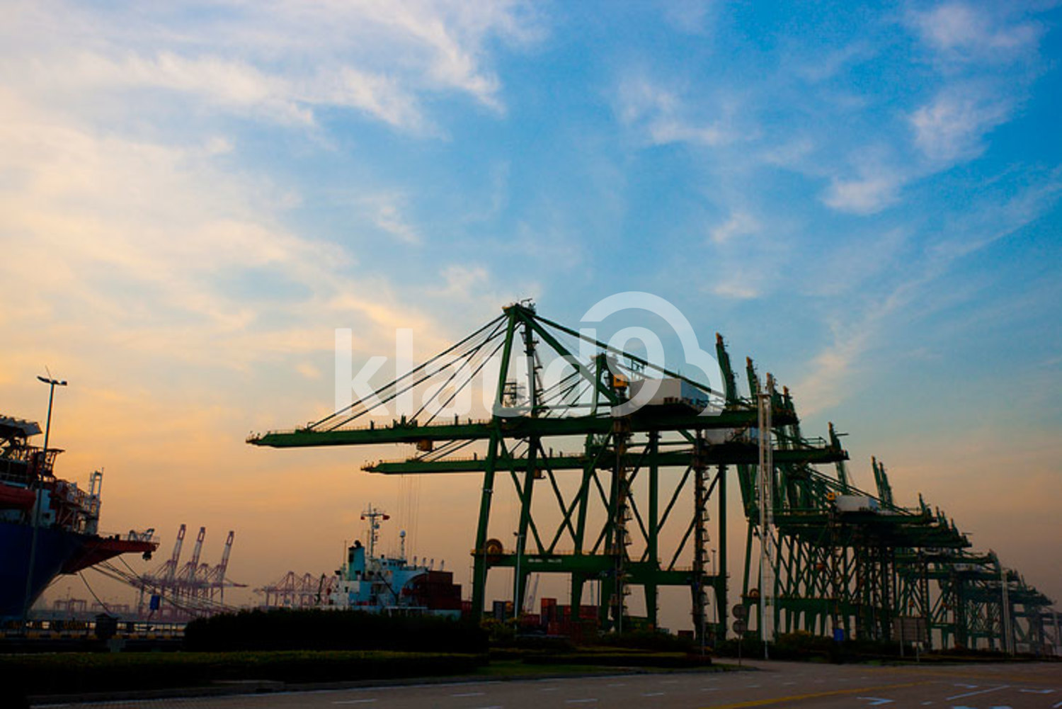 View of cranes and cargo ships at dusk