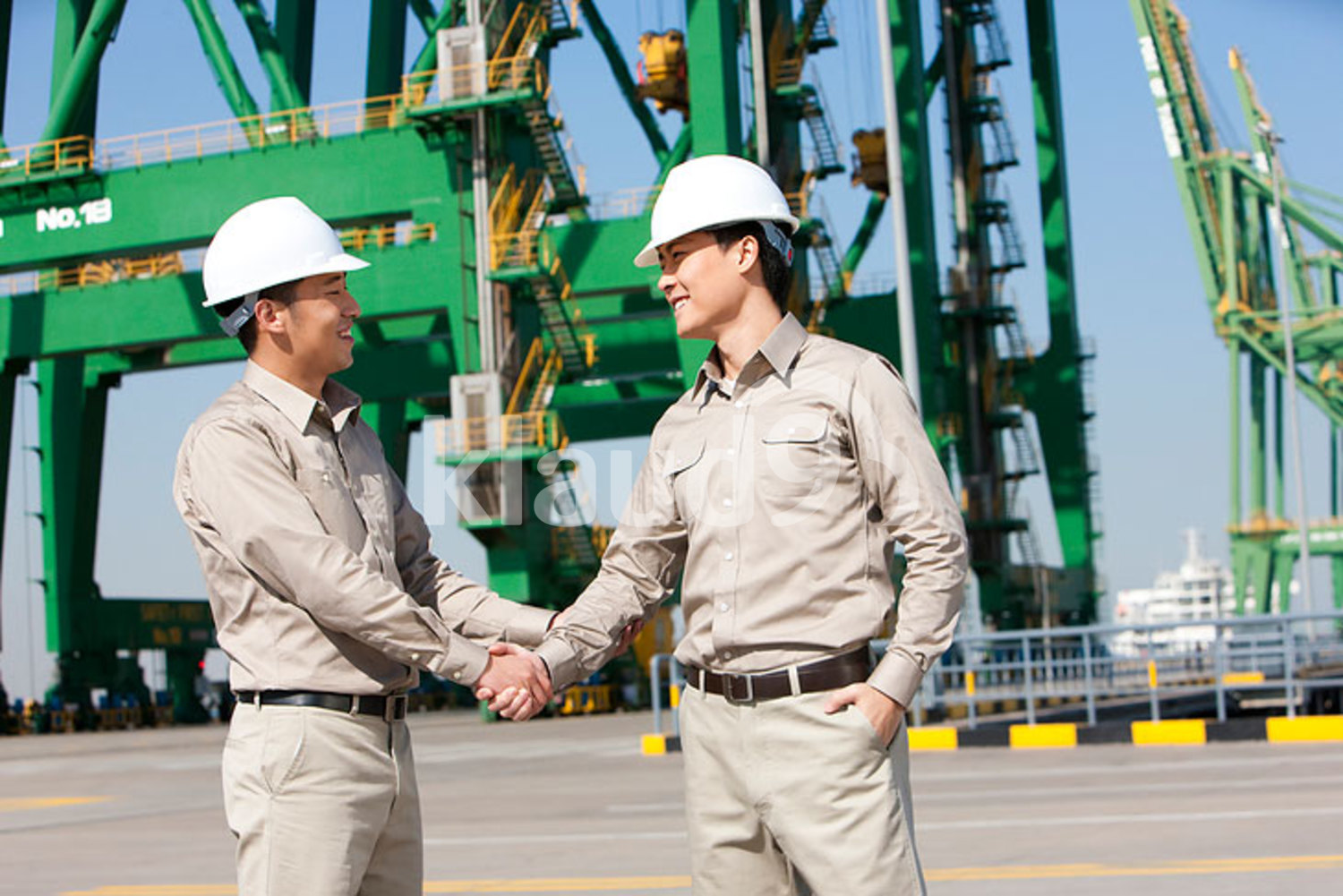 Male Chinese shipping industry workers shaking hands