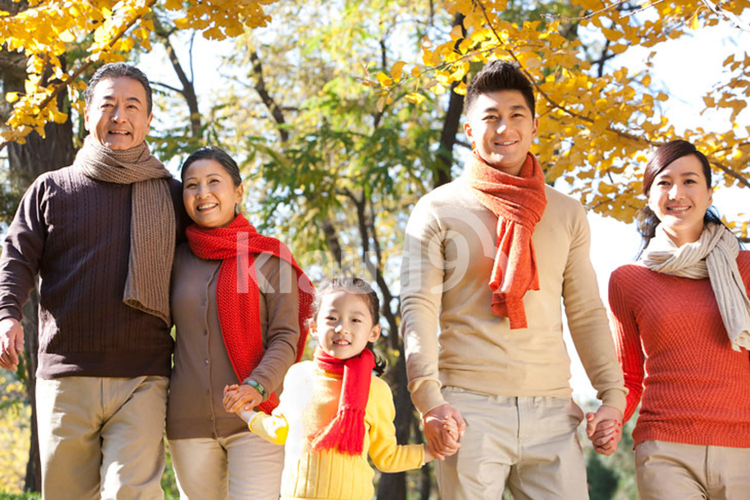 Chinese family walking in a park in autumn