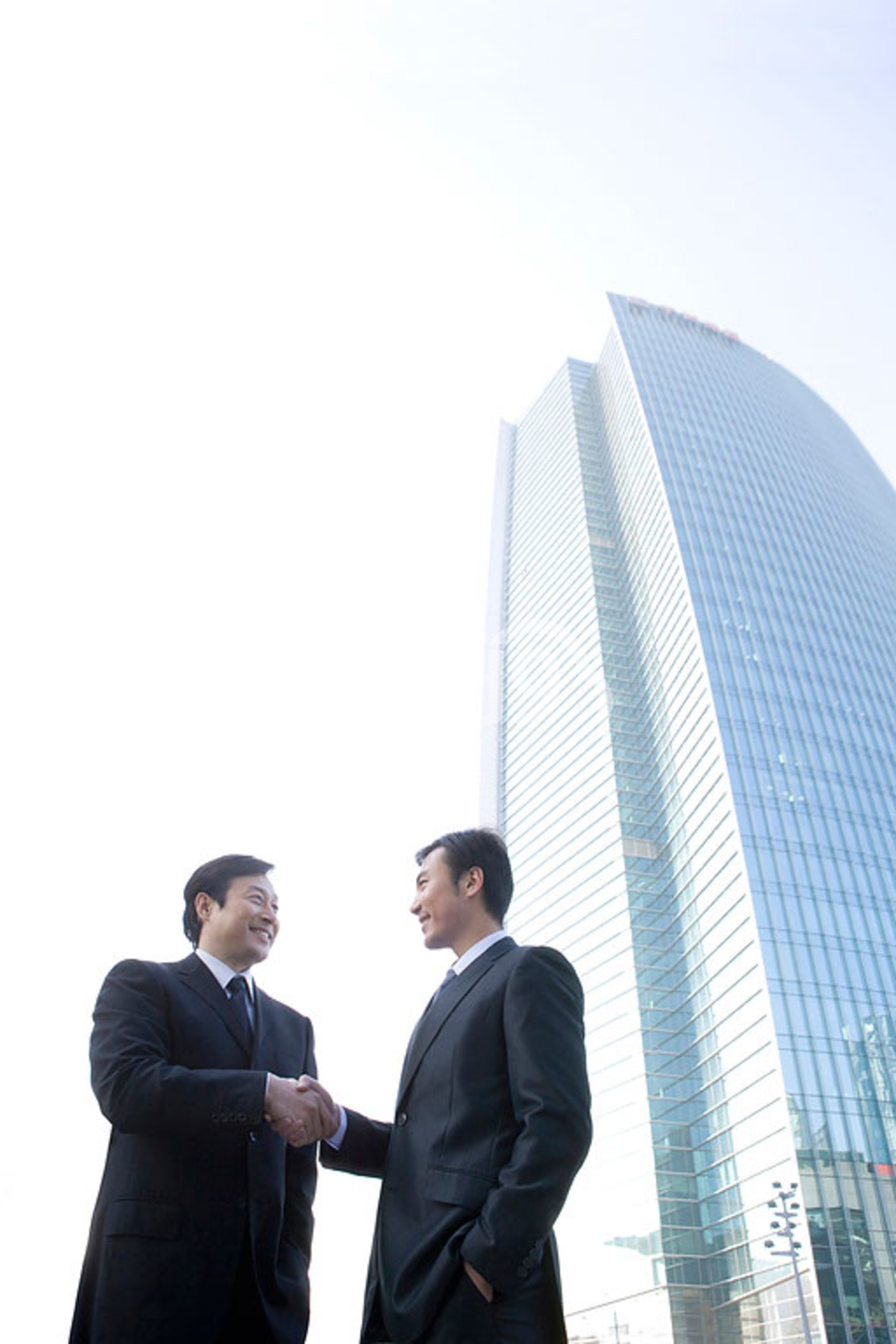 Chinese businessmen shaking hands in front of tall building