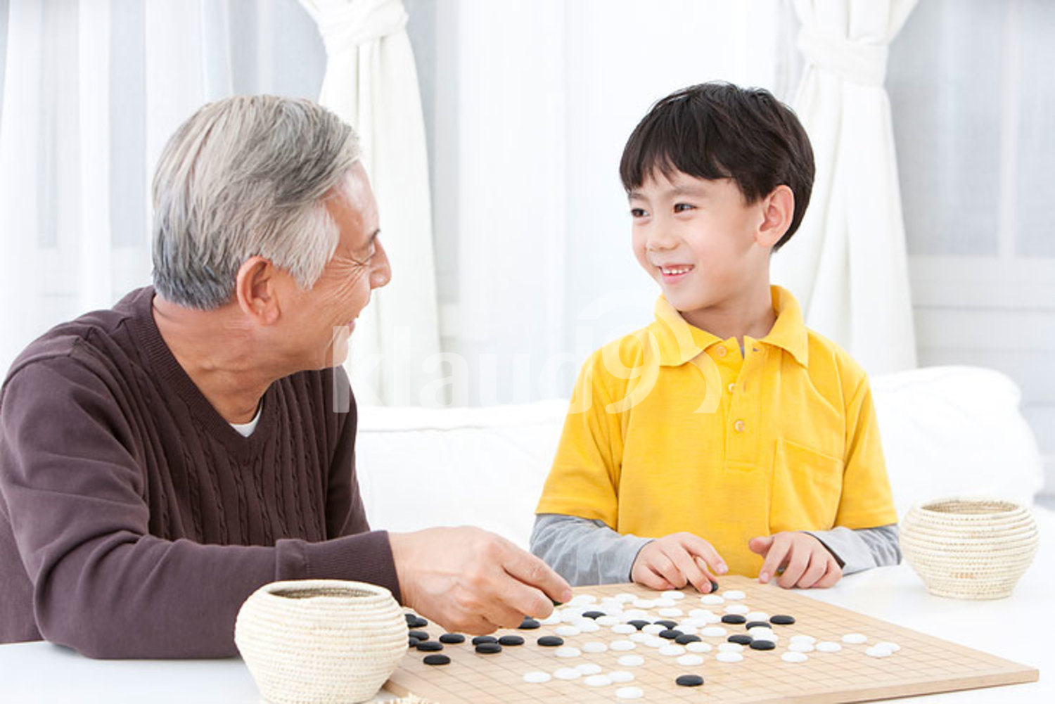 Chinese grandpa and grandson playing the game of Go