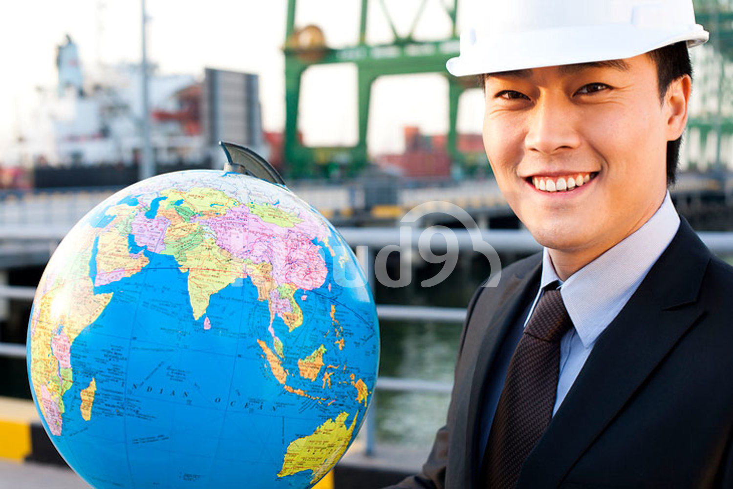 Chinese businessman with a globe at a shipping port