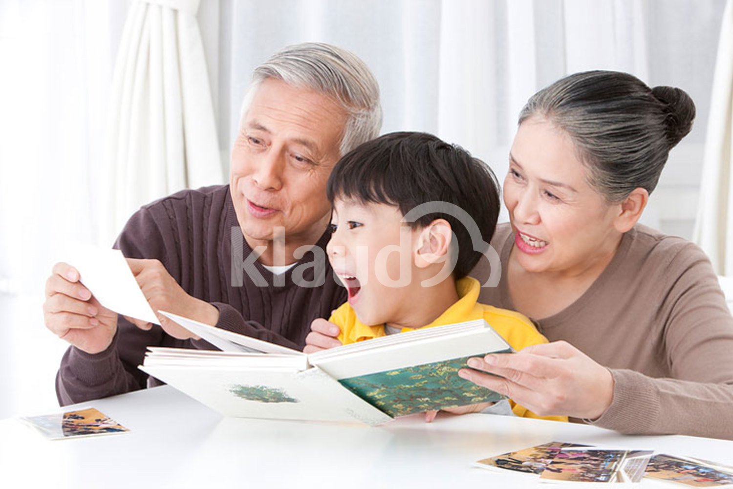 Chinese grandparents and grandson looking through family album