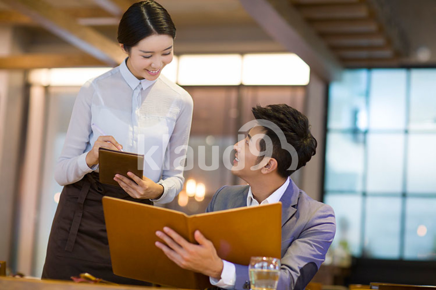 Young Chinese man ordering in restaurant