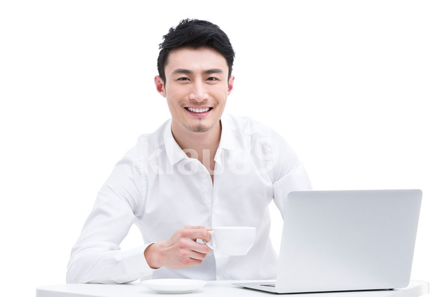 Chinese businessman using laptop whilst drinking coffee from cup