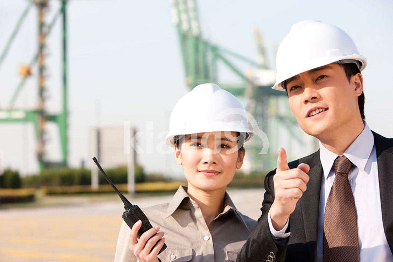 Chinese businessman with shipping industry worker in discussion