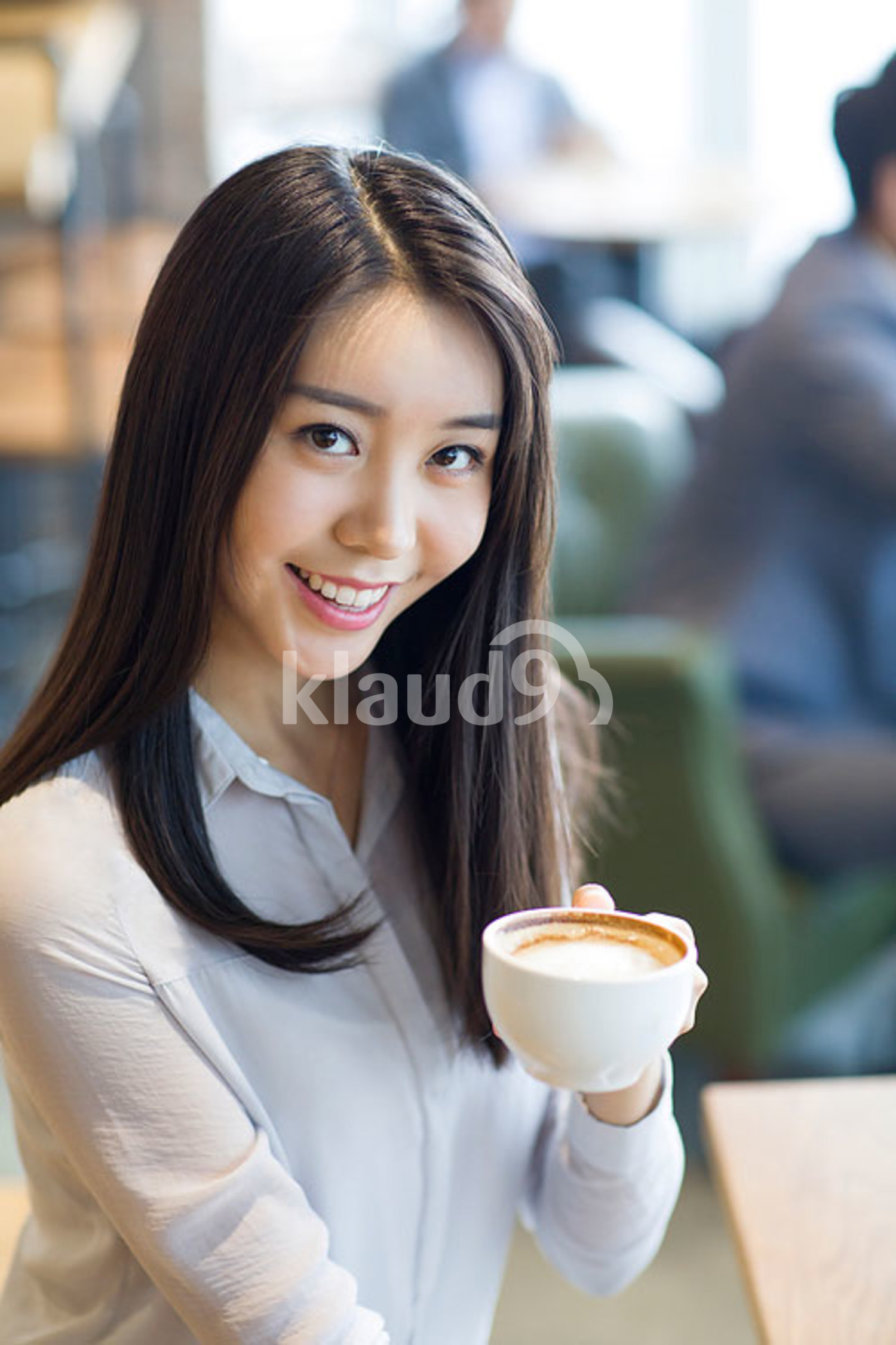 Young Chinese woman drinking coffee in café