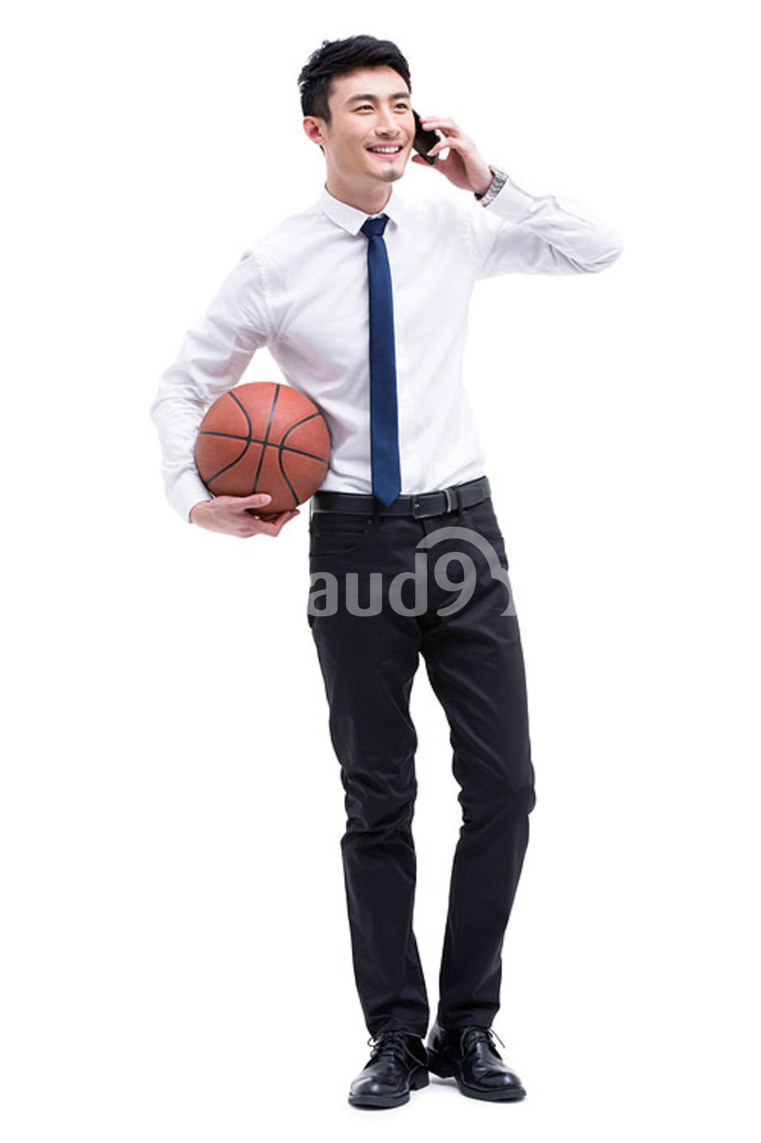 Young Chinese businessman talking on the phone while holding a basketball