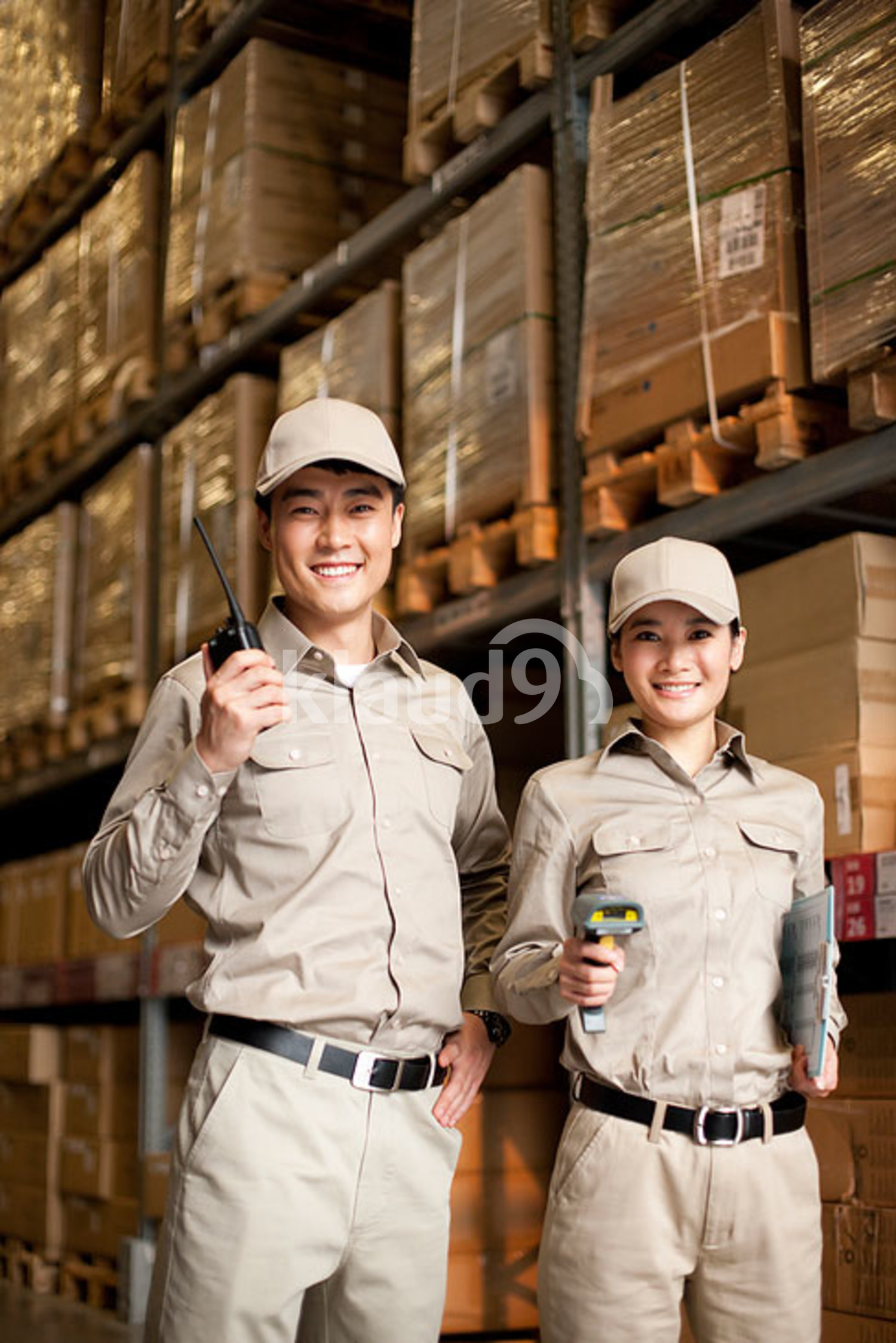 Male and female Chinese warehouse workers in full uniform