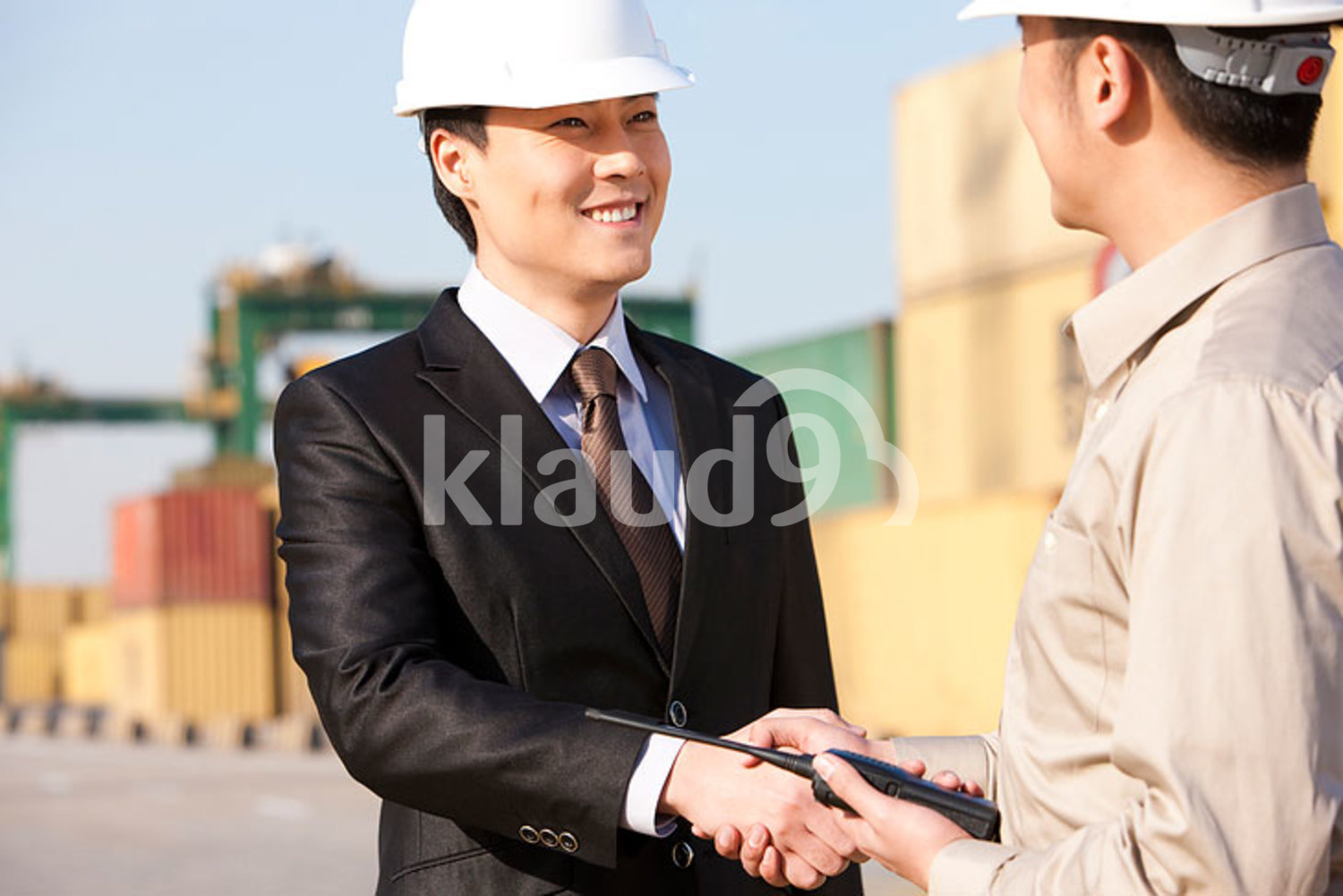 Chinese businessman and shipping industry worker shaking hands