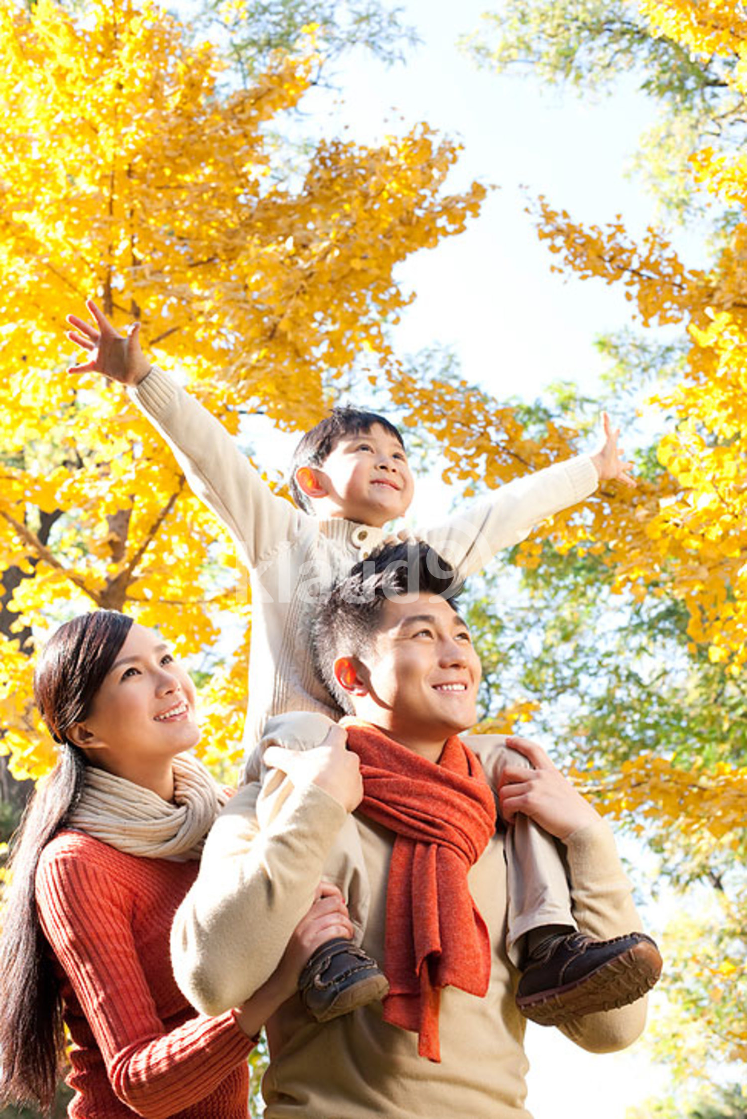 Chinese boy sitting on his father's shoulders in a park with family in autumn