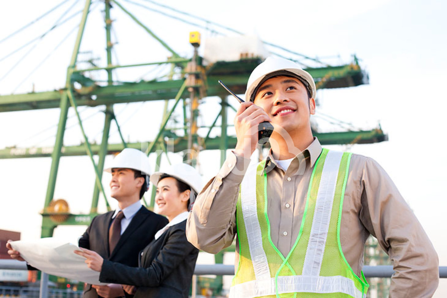 Chinese shipping industry worker using a walkie-talkie with businesspeople looking over blueprints in the background