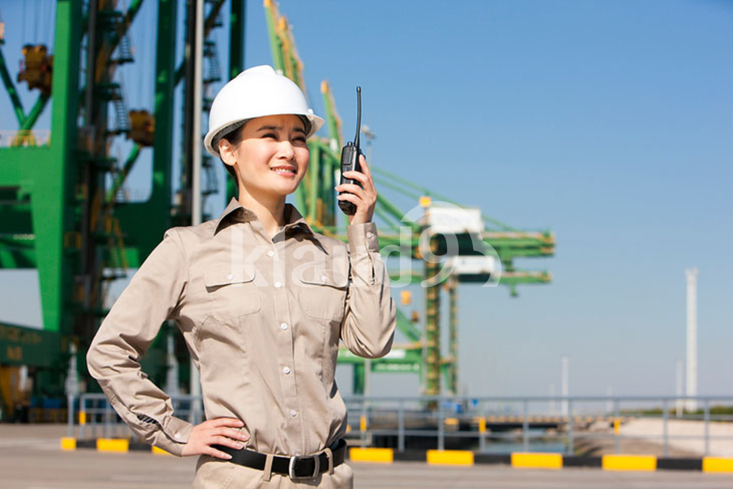 Female Chinese shipping industry worker with walkie-talkie