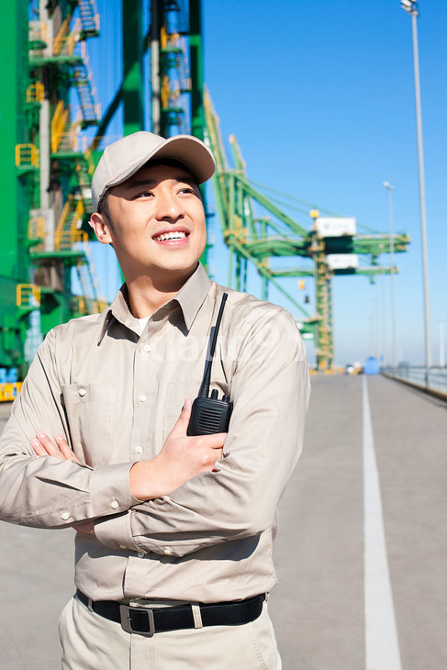 Male Chinese shipping industry worker with walkie talkie