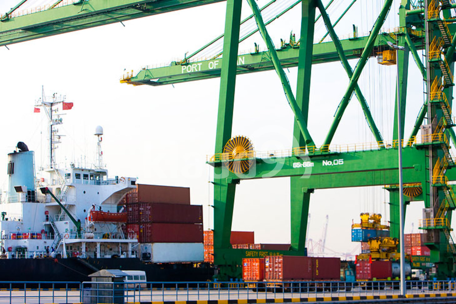 Cargo ship with cranes and cargo containers in shipping port