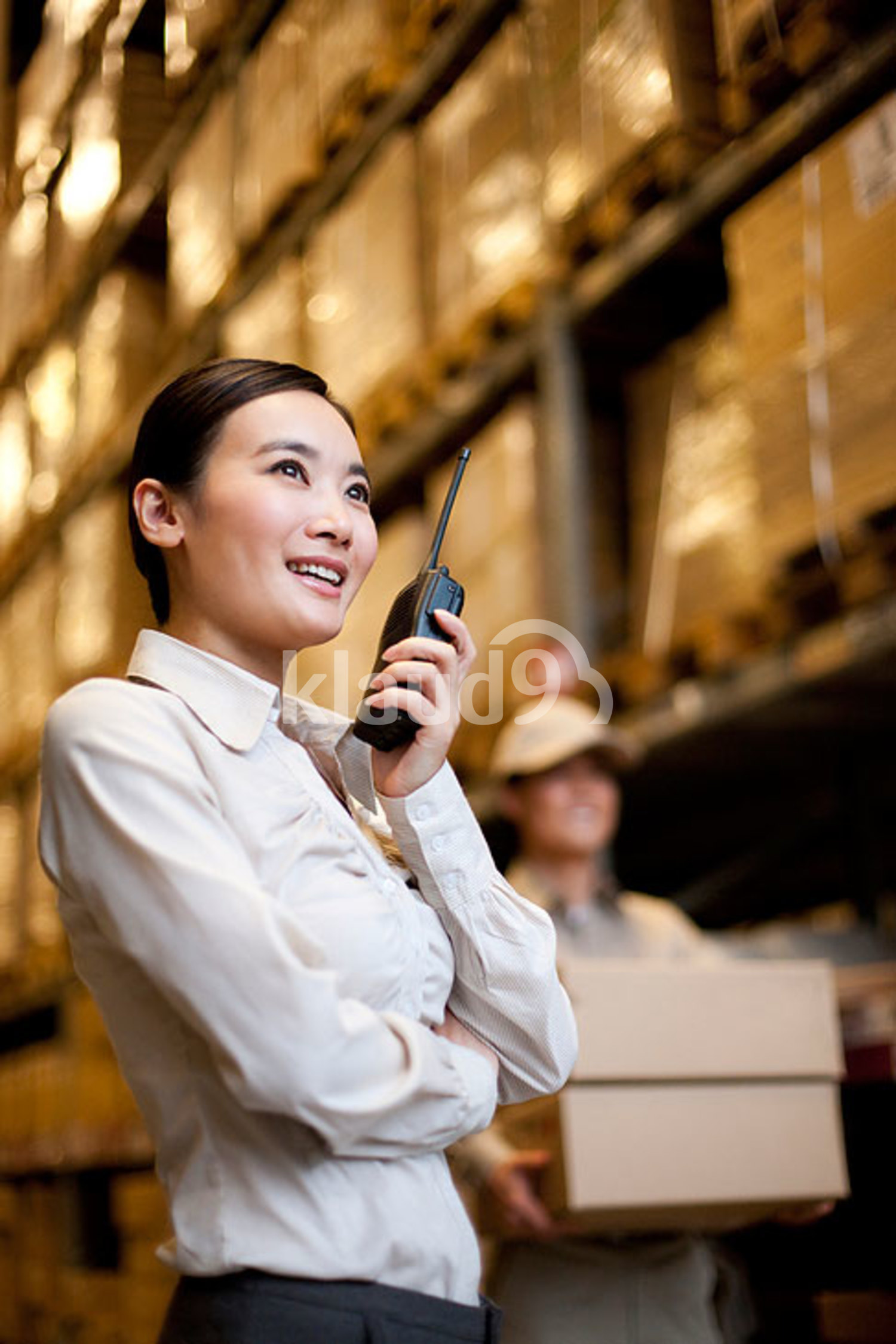 Chinese businesswoman in a warehouse with a walkie-talkie