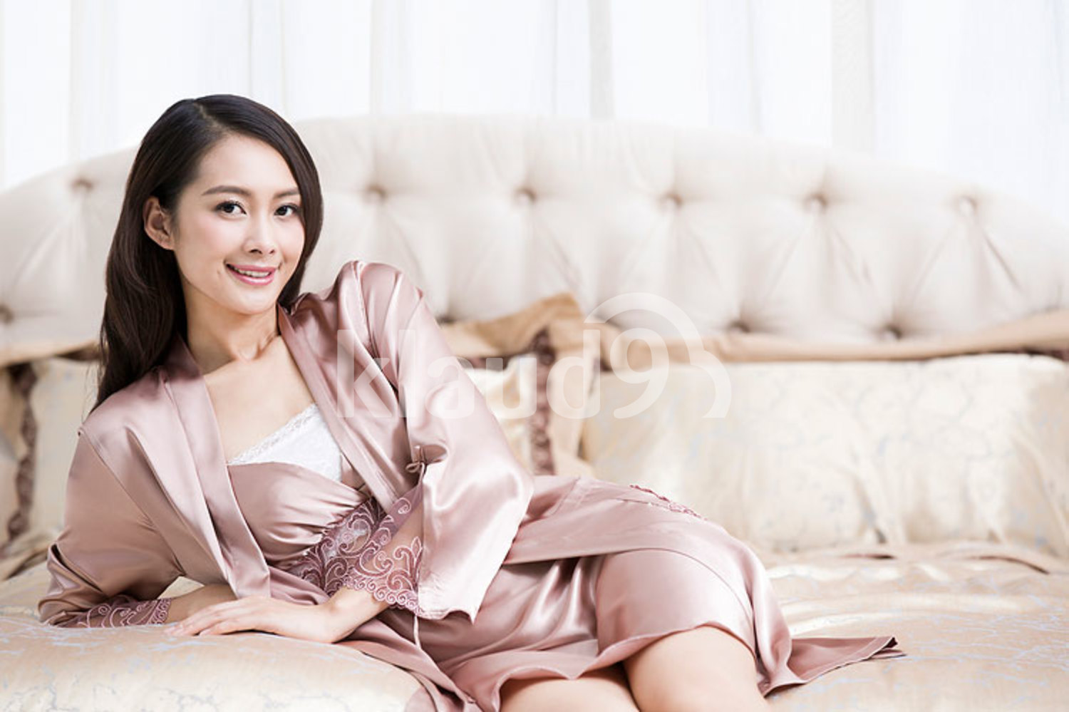 Beautiful young Chinese woman in bedroom