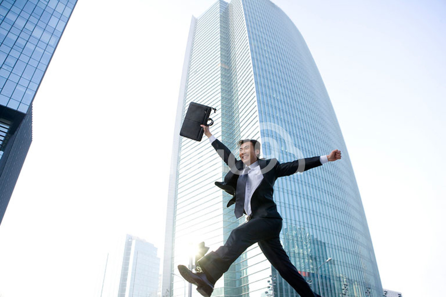 Chinese businessman jumping in front of tall building