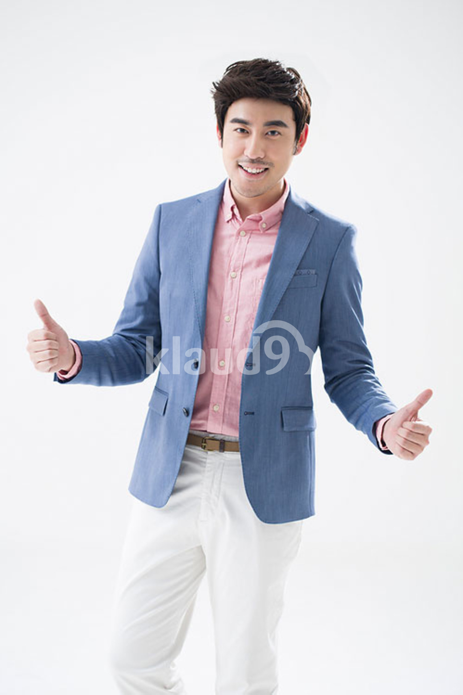 Fashionable young Chinese man doing thumbs up