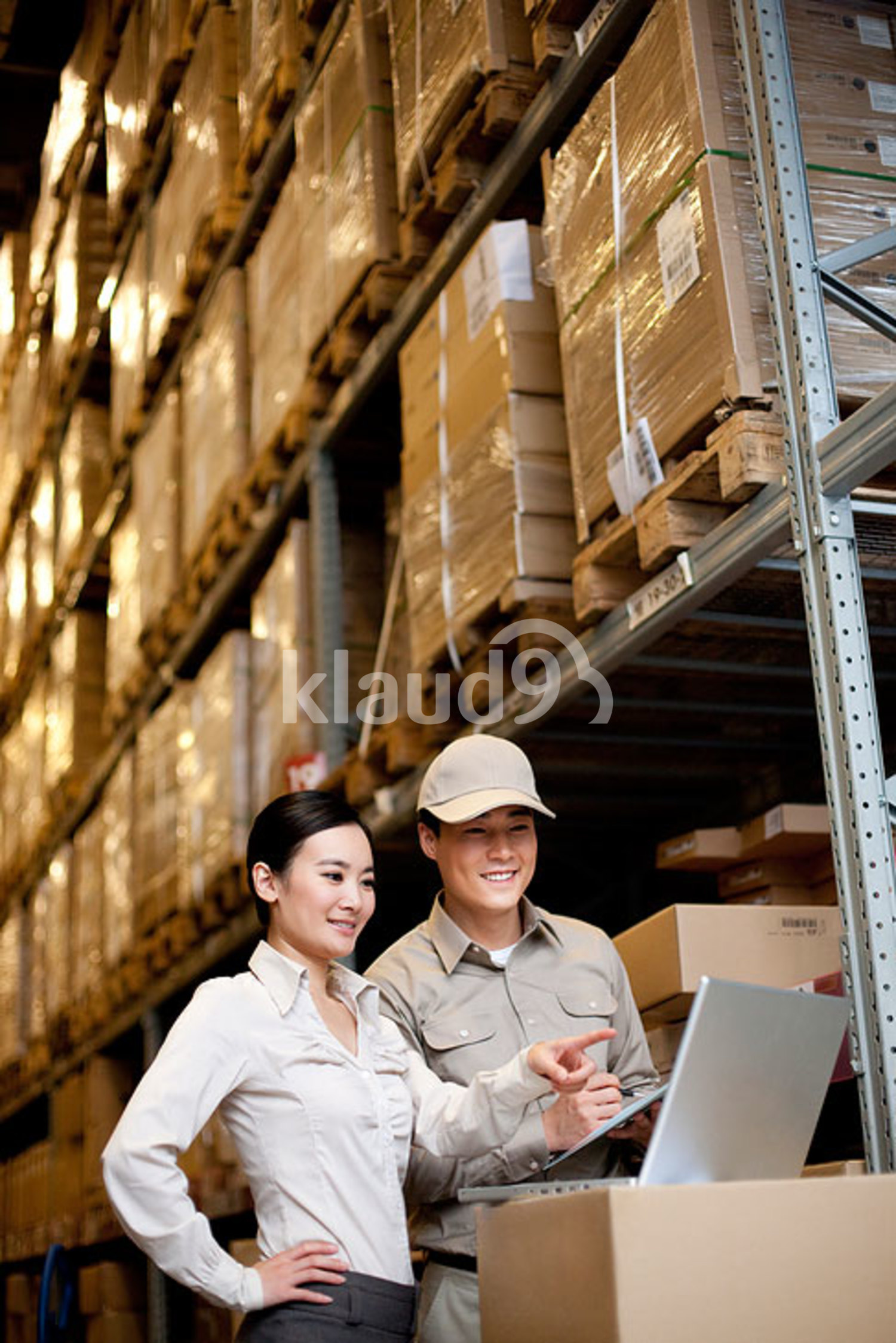 Chinese businesswoman in a warehouse with worker using a laptop