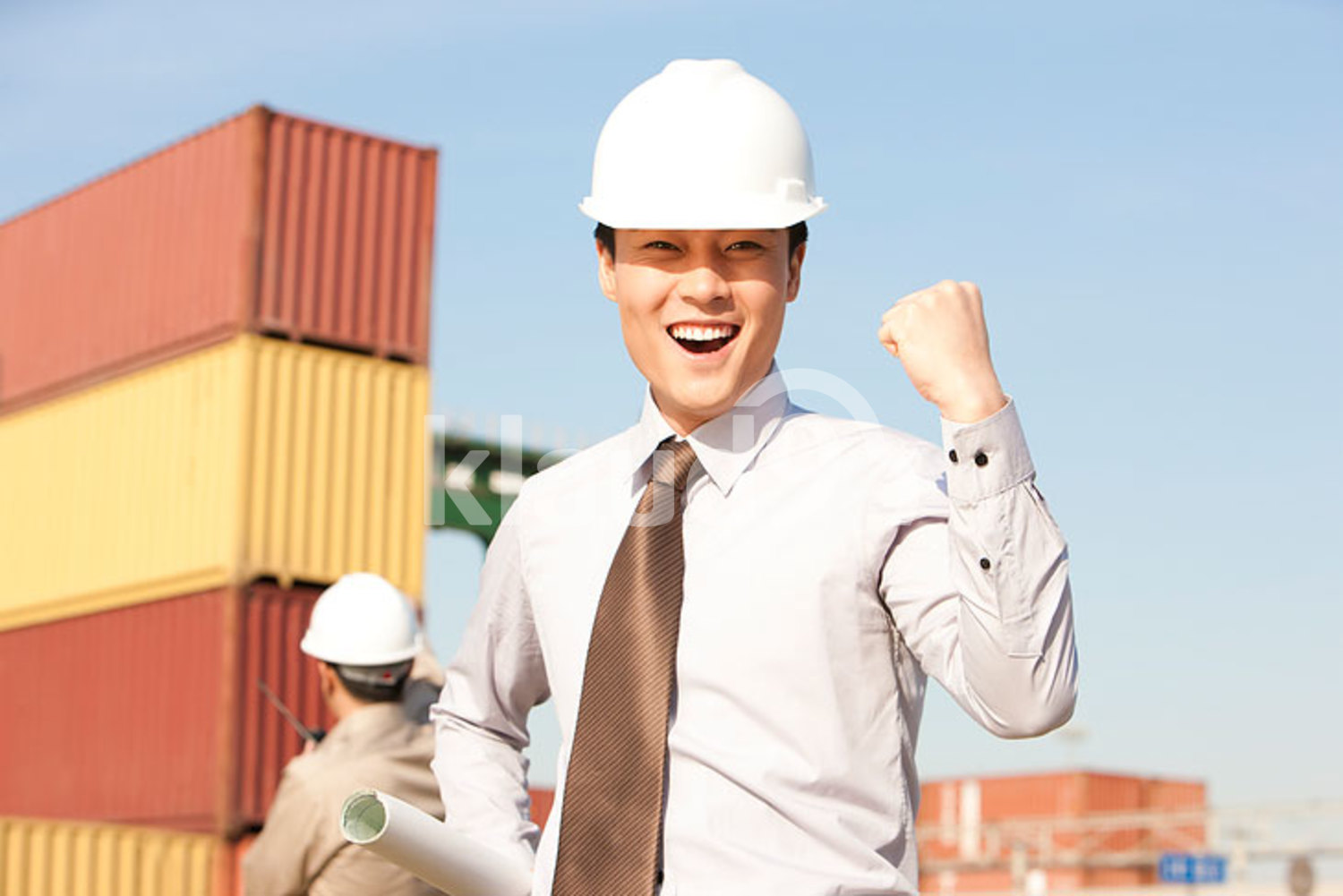 Chinese businessman with raised fist with cargo containers in the background