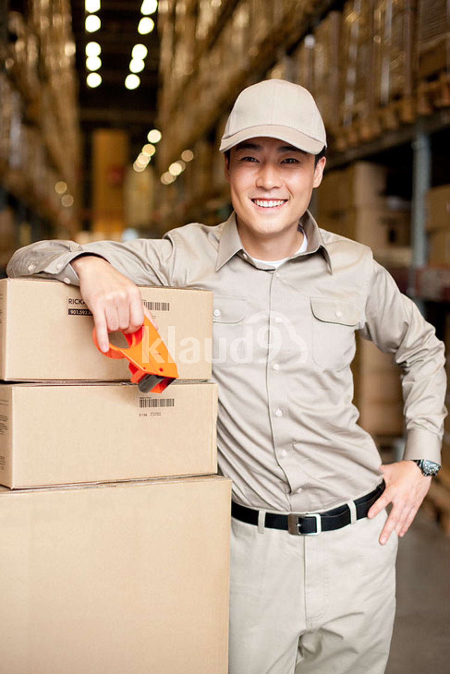 Male Chinese warehouse worker with packed boxes