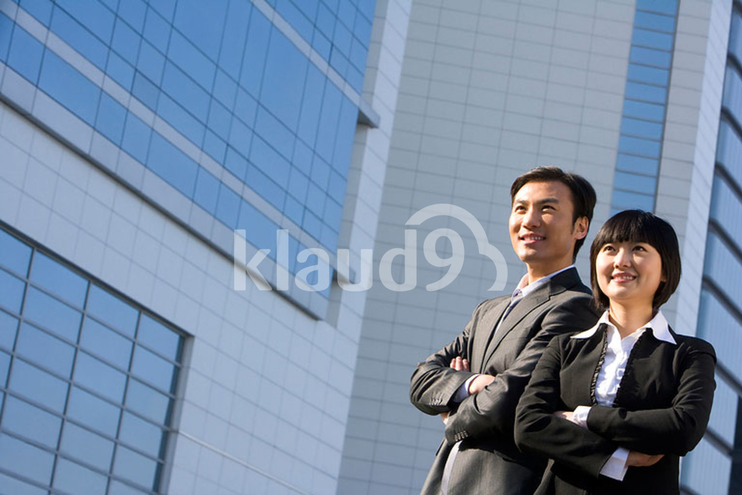Chinese businessman and businesswoman standing in front of tall building