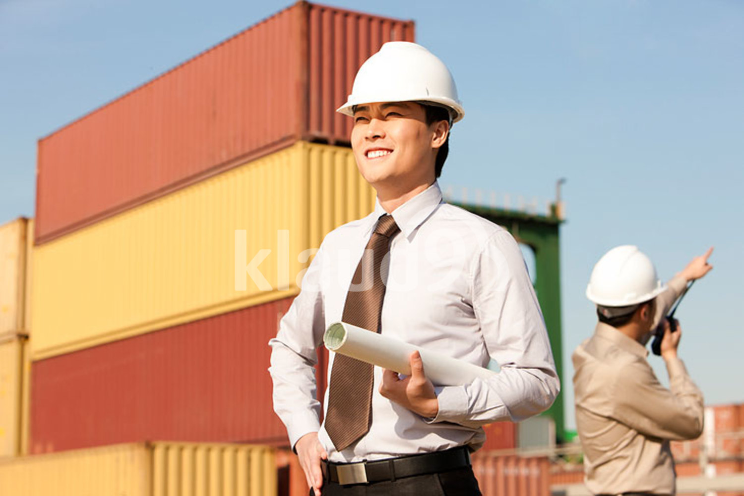 Chinese businessman with blueprints and shipping industry worker using his walkie-talkie